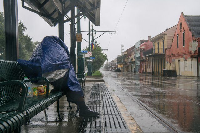A person sits at a train stop for shelter ahead of Hurricane Ida on August 29, 2021 in New Orleans, Louisiana. Residents of New Orleans continue to prepare as the outer bands of the hurricane begin to cut across the city. Ida is expected to make landfall as a Category 4 storm later today. (Photo by Brandon Bell/Getty Images)