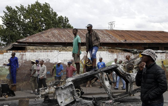 A crowd of anti-immigrant protesters stand on a burned-out car outside the Jeppe hostel in Johannesburg, South Africa, Friday, April 17, 2015, where some foreigners have sought refuge. Several shops and cars owned by foreigners were torched in downtown Johannesburg overnight in continued anti-immigrant attacks. (Photo by Themba Hadebe/AP Photo)