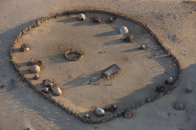 An aerial view of a livestock enclosure of the Himba people, in October, 2014, in the Namib Desert, Namibia. (Photo by Theo Allofs/Barcroft Media)