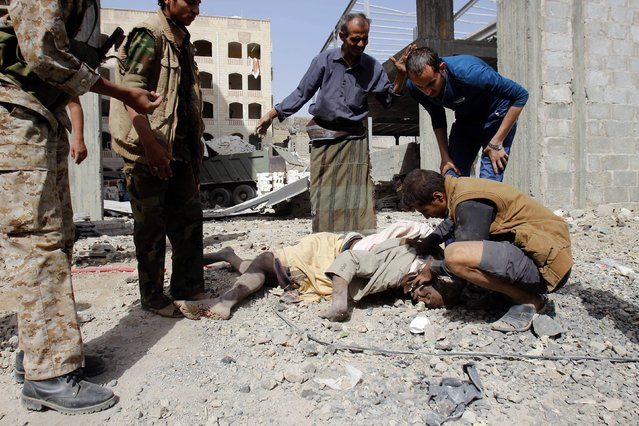 Yemenis checks the body of a man killed in a Saudi-led airstrike against Iran-allied Shiite rebels, known as Houthis, that hit a site of a weapons cache in Yemen's capital, Sanaa, Monday, April 20, 2015. The strikes on Yemen's rebel-held capital on Monday caused massive explosions that shattered windows, sent residents scrambling for shelter and killed a local TV presenter. (Photo by Hani Mohammed/AP Photo)