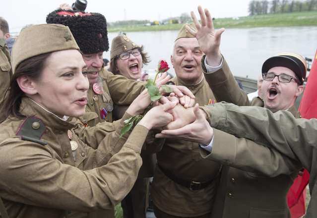 Amateur actors put their hands together during a re-enacting of the link-up of Soviet and American troops at the 70th anniversary of the Elbe Day in Torgau, eastern Germany, Saturday, April 25, 2015. (Photo by Jens Meyer/AP Photo)