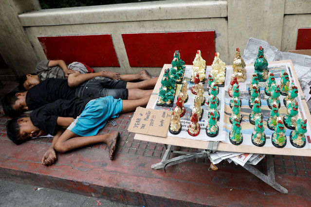 Homeless teenagers sleep on a sidewalk next to miniature rooster statues for sale on the eve of Lunar New Year in Manila's Chinatown, the Philippines January 27, 2017. (Photo by Erik De Castro/Reuters)