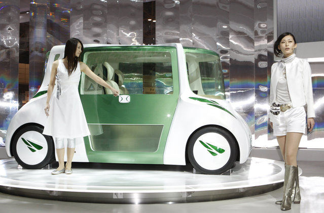 Models pose with Toyota Motor Corp's RiN concept vehicle, a car designed to promote healthy living with seats that make the driver and passengers sit upright, a steering wheel that senses the driver's mood and visual displays to promote calm during the 40th Tokyo Motor Show in Chiba Wednesday, October 24, 2007. (Photo by Kim Kyung-Hoon/Reuters)