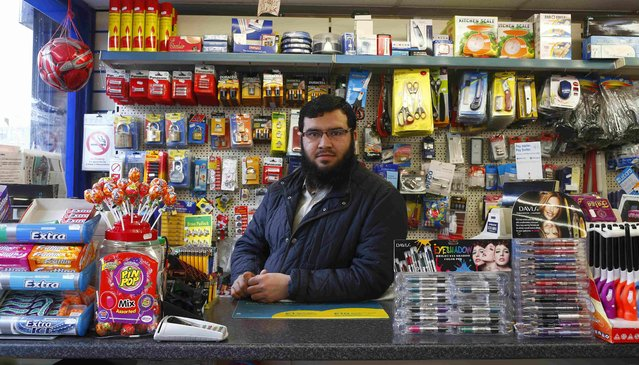 "Fawad Ali, 26, poses for a photograph at his workplace, Pound Plus Express, in the London constituency of Brent Central, Britain April 3, 2015. Ali, who was born in Pakistan, said: ""I listened to the debate and I think Ed is doing very well. I think Labour will take most of the seats but will have to share power with someone. I really like the Respect party but they are not challenging here"". (Photo by Eddie Keogh/Reuters)"