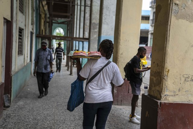 A woman walks down the street carrying a tray of cakes in Havana, Cuba, Monday, July 26, 2021. (Photo by Eliana Aponte/AP Photo)