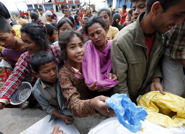 People queue for food handouts after Saturday's earthquake near Chautara, Nepal, April 29, 2015. (Photo by Olivia Harris/Reuters)