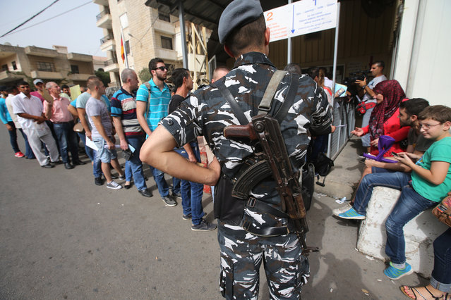 In this Friday, September 11, 2015, file photo, a Lebanese policeman stands guard as Syrian citizens line up to apply for visas, outside the German embassy, in Rabieh, north Beirut, Lebanon. (Photo by Hussein Malla/AP Photo)