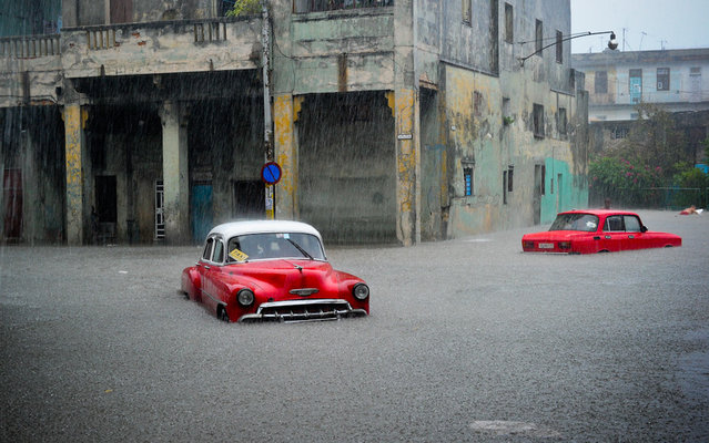 Stranded cars remain in a flooded street during an intense rainstorm in Havana, on April 29, 2015.  Two people were killed, three buildings collapsed and another 24 suffered some kind of damage due to the heavy rain that affected several sectors of Havana Wednesday. (Photo by Yamil Lage/AFP Photo)