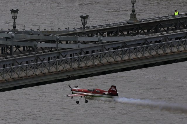 Zoltan Veres of Hungary flies his airplane under the Chain Bridge during an air show in Budapest, Hungary, May 1, 2015. (Photo by Bernadett Szabo/Reuters)