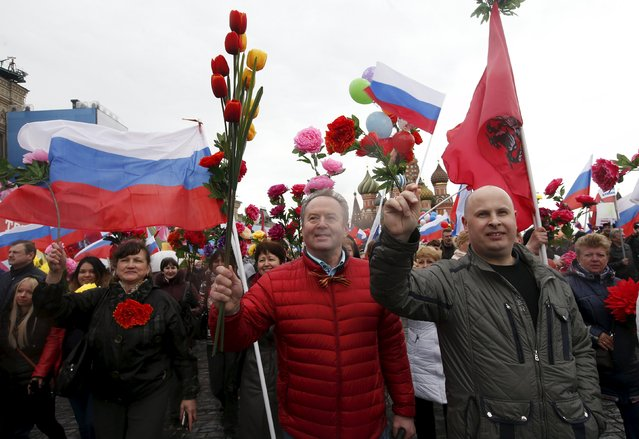 People walk with flags and artificial flowers at Red Square during a May Day rally in Moscow May 1, 2015. (Photo by Maxim Zmeyev/Reuters)