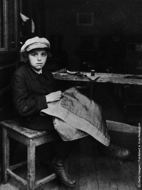 circa 1915:  A Jewish boy sewing at his home in East London