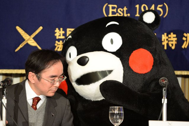 Kumamon gestures to brand officer for the Kumamoto prefecture government, Masataka Naruo (L) during a press conference at the foreign correspondents' club in Tokyo on February 15, 2014. (Photo by Toshifumi Kitamura/AFP Photo)