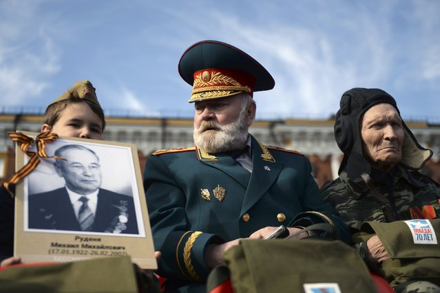 Veterans and a boy wait for the Victory Day parade at Red Square in Moscow, Russia, May 9, 2015. (Photo by Reuters/Host Photo Agency/RIA Novosti)