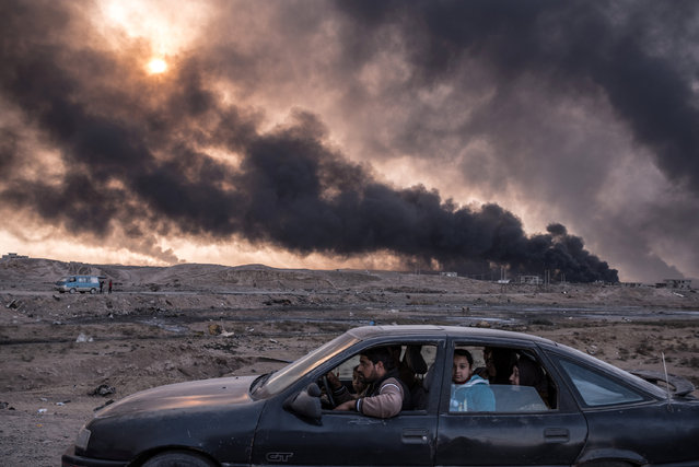 A family flees the fighting in Mosul, Iraq's second-largest city, as oil fields burned in Qayyara, Iraq, on November 12, 2016. In its sixth week, the military campaign to retake Mosul from the Islamic State had bogged down in a grueling fight. Seeking to escape the bloodshed, more civilians than ever took the risk of evacuation, hoping to find help if they could make it past the militants' gun range. By mid-December 2016, up to one million people were trapped inside the city, running low on food and drinking water and facing the worsening cruelty of Islamic State fighters. (Photo by Sergey Ponomarev/Reuters/Courtesy of World Press Photo Foundation)