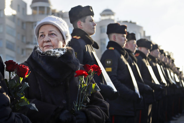 Women with flowers stand next to Belarusian military cadets holding portraits of soldiers who were killed during the Soviet war in Afghanistan, during a ceremony at memorial on the Island of Tears in Minsk, Wednesday, February 15, 2017. The ceremony was held to mark the 28th anniversary of the Soviet pullout from Afghanistan. (Photo by Sergei Grits/AP Photo)