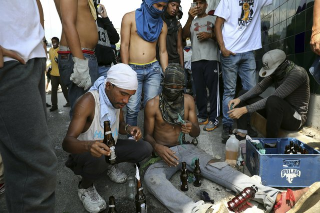 Anti-government protesters prepare molotov cocktails outside La Carlota airbase during clashes between the two sides in Caracas, Venezuela, Wednesday, May 1, 2019. (Photo by Rodrigo Abd/AP Photo)