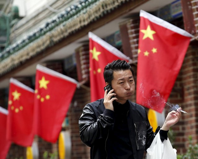 A smoker walks past Chinese national flags in front of a restaurant in Beijing, China, May 11, 2015. China is set to raise the wholesale tax rate for cigarettes to 11% from 5%, the Ministry of Finance said on Friday, in a move to deter smokers in the world's biggest maker and consumer of tobacco. (Photo by Kim Kyung-Hoon/Reuters)