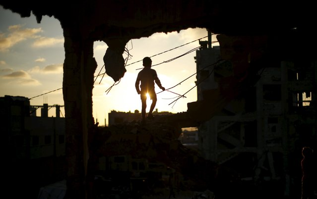 A Palestinian boy plays at a house that witnesses said was destroyed during the 50-day war last summer, in the east of Gaza City May 4, 2015. (Photo by Mohammed Salem/Reuters)