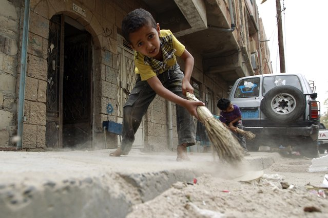 Yemeni children sweep the pavement littered with rubbish as garbage trucks hardly run due to an acute shortage of fuel in the capital Sanaa, on May 4, 2015. (Photo by Mohammed Huwais/AFP Photo)