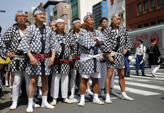 Revellers wear traditional short coats as they watch a portable shrine paraded through a street during the Sanja Matsuri festival in the Asakusa district of Tokyo May 17, 2015. (Photo by Thomas Peter/Reuters)