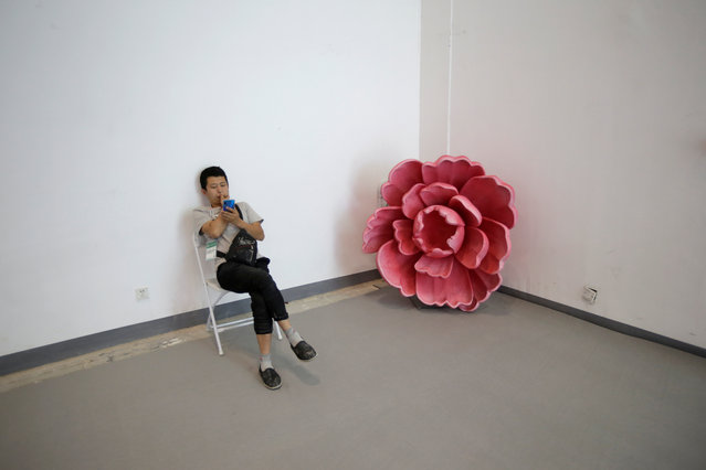 A man rests next to a decoration at China International Fair for Trade in Services in Beijing, China, May 28, 2019. (Photo by Jason Lee/Reuters)