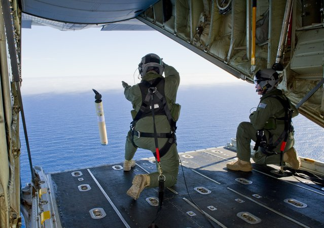 A photo taken on March 20, 2014, shows Royal Australian Air Force Loadmasters, Sergeant Adam Roberts (L) and Flight Sergeant John Mancey (R), preparing to launch a Self Locating Data Marker Buoy from a C-130J Hercules aircraft in the southern Indian Ocean as part of the Australian Defence Force's assistance to the search for Malaysia Airlines flight MH370.  (Photo by Leading Seaman Justin Brown/AFP Photo/Australian Defence)