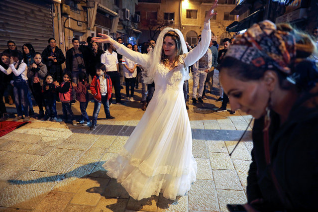 A woman dances as Arab and Jewish players compete in a backgammon championship organised by Double Yerushalmi, a group trying to build closer ties between Arabs and Jews through cultural activities, in Jerusalem February 27, 2017. (Photo by Ammar Awad/Reuters)