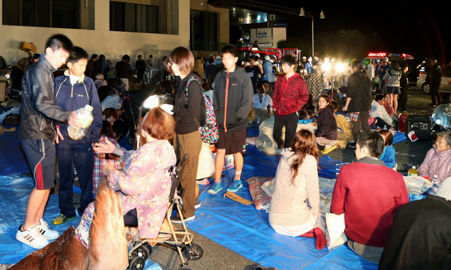Stranded people gather outside a town hall of Mashiki, after an earthquake in Kumamoto, southern Japan, Thursday, April 14, 2016. (Photo by Kyodo News via AP Photo)