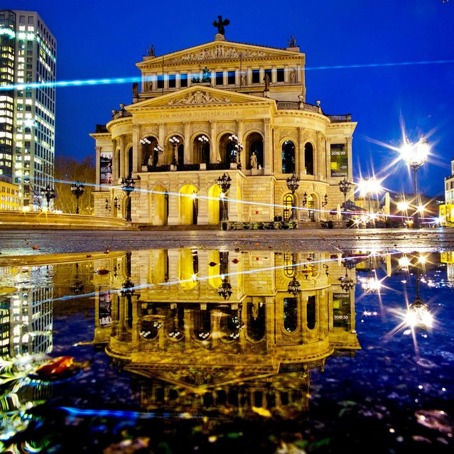 The Old Opera is reflected in a puddle in Frankfurt, Germany, early Friday, April 5, 2019. (Photo by Michael Probst/AP Photo)