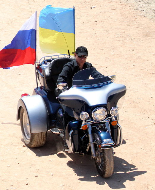 Vladimir Putin rides a motor tricycle as he attends an international bike show festival on July 24, 2010 in the Black Sea resort of Sevastopol, Ukraine. (Photo by Sasha Mordovets/Getty Images)