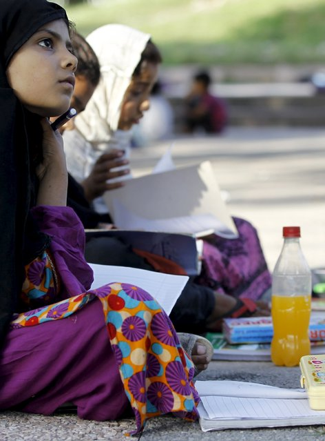 A student listens to her teacher during class at a local park in Islamabad April 22, 2015. (Photo by Caren Firouz/Reuters)