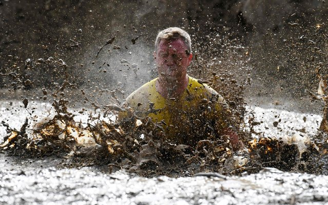 A runner jumps in a mud pit as he takes part in the Mud Day, a 13km race with obstacles in Beynes, near Paris on June 16, 2019. (Photo by Alain Jocard/AFP Photo)