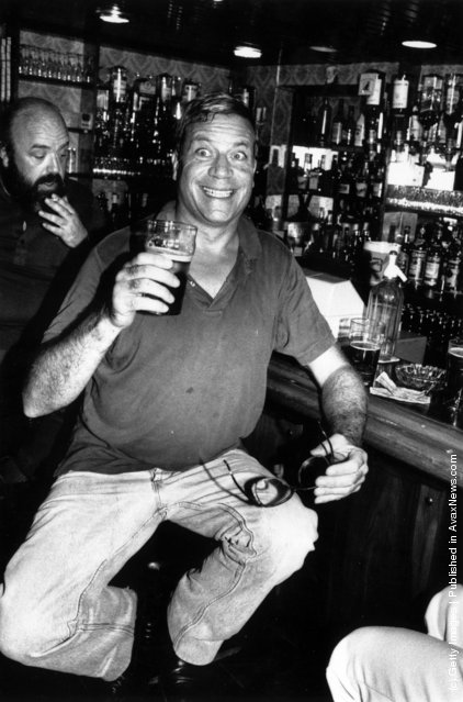 1984: Film star Oliver Reed pulls a face for the photographer  while enjoying a pint of beer in a well stocked bar