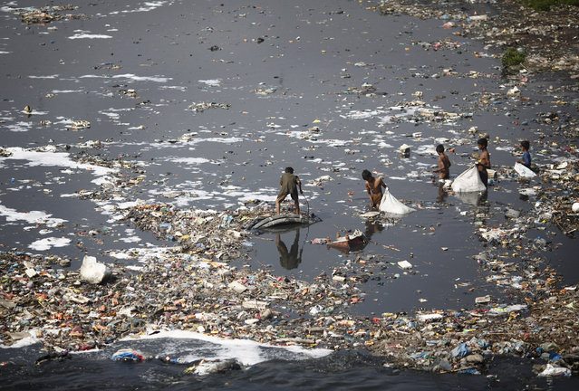 """Children look for plastic bottles at the polluted Bagmati River in Kathmandu, Nepal on March 22, 2013. This year's theme for World Water Day, which falls on March 22, is """"Water Cooperation"""" and is in line with the celebration of the International Year of Water Cooperation. (Photo by Navesh Chitrakar/Reuters)"""