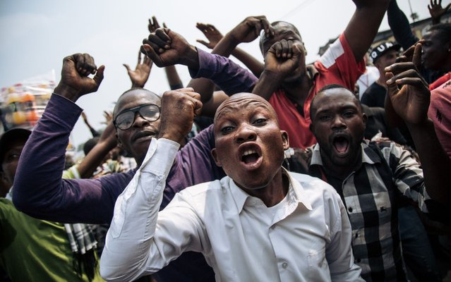 Supporters of the former candidate of the Lamuka opposition coalition, Martin Fayulu, shout in protest after the protest march organized on June 30, 2019, the Independence Day, in Kinshasa was stopped by the police. Police in the DR Congo capital Kinshasa used teargas on June 30 to break up an opposition march and blocked a car transporting former presidential candidate Martin Fayulu. (Photo by Alexis Huguet/AFP Photo)