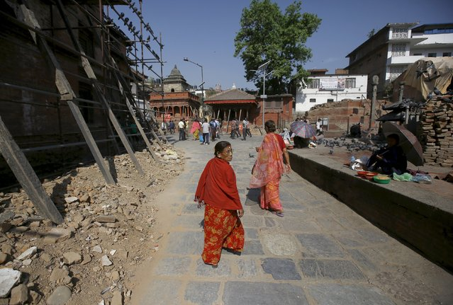 Women walk past the debris of collapsed temples at Hanumandhoka Durbar Square during the first anniversary of the earthquake in Kathmandu, Nepal, April 24, 2016. (Photo by Navesh Chitrakar/Reuters)