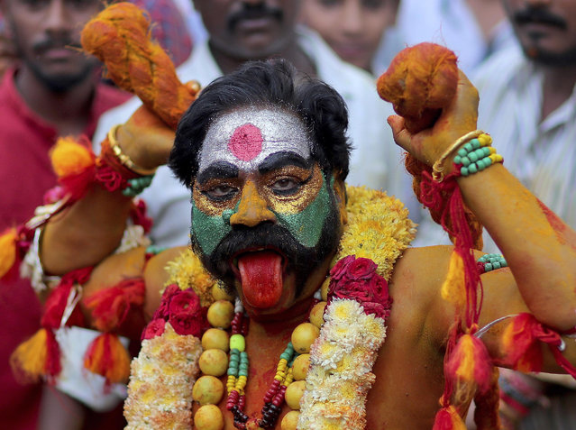 "A devotee of Hindu goddess Kali performs a ritual during the ""Bonalu"" festival in Hyderabad, India, Sunday, July 28, 2019. Bonalu is a month-long Hindu folk festival of the Telangana region dedicated to Kali, the Hindu goddess of destruction. (Photo by Mahesh Kumar A./AP Photo)"