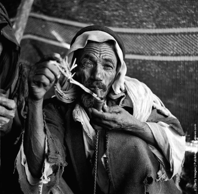1950: An elderly Arab Bedouin sits loading and smoking a pipe
