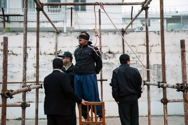 Balal, who killed Iranian youth Abdolah Hosseinzadeh in a street fight with a knife in 2007, reacts as he stands in the gallows during his execution ceremony in the northern city of Nowshahr on April 15, 2014. Samereh Alinejad, the mother of Abdolah Hosseinzadeh spared the life of Balal, her son's convicted murderer, with an emotional slap in the face as he awaited execution prior to removing the noose around his neck. (Photo by Araash Khamooshi/AFP Photo/ISNA)