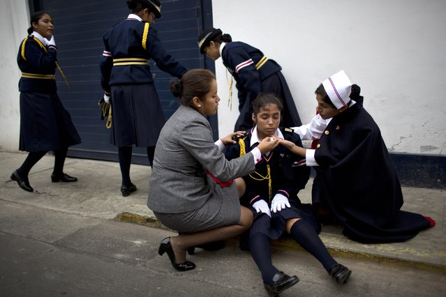 A student is assisted by teachers after she fell ill while marching in a parade celebrating Saint Peter's day in Lima, Peru, Monday, June 29, 2015. (Photo by Rodrigo Abd/AP Photo)