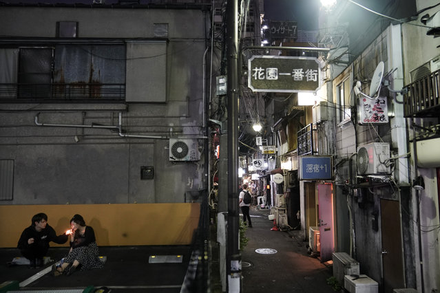 A couple smokes cigarettes in a parking lot adjacent to the Golden Gai in the Shinjuku district of Tokyo, July 28, 2019. (Photo by Jae C. Hong/AP Photo)