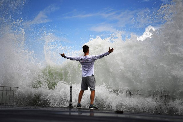 A man reacts as waves crash against the seafront on Enoshima Island on the coast of Kanagawa prefecture, southwest of Tokyo, on August 13, 2019. (Photo by Charly Triballeau/AFP Photo)