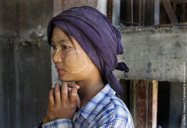 A Burmese woman, who is a construction worker, takes a break from carrying bags of cement