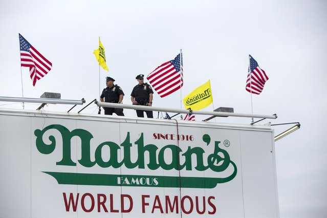 New York Police Officers stand guard on a rooftop during the annual Fourth of July 2015 Nathan's Famous Hot Dog Eating Contest in Brooklyn, New York July 4, 2015. New York Governor Andrew Cuomo ordered heightened security measures across the state over the U.S. July Fourth holiday weekend in response to a call for vigilance by the federal government. (Photo by Andrew Kelly/Reuters)