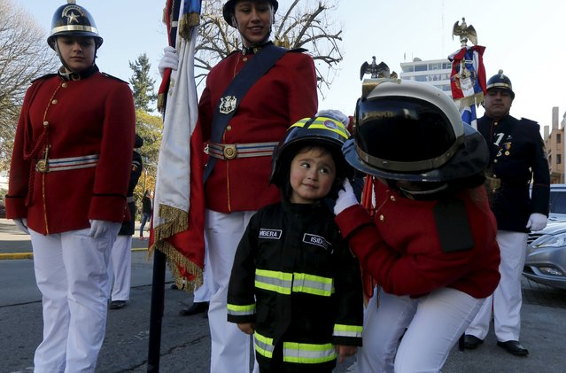 A firewoman speaks to a child dressed as a firefighter during a parade to celebrate Firemen's Day, in Concepcion, Chile, June 28, 2015. (Photo by Mariana Bazo/Reuters)