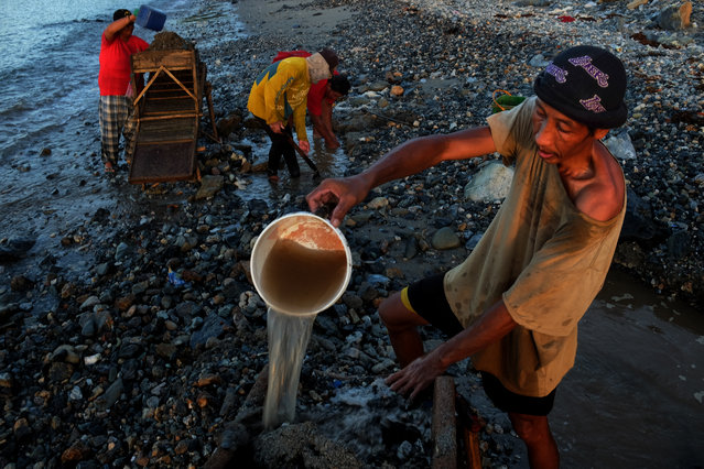 A family digs and sifts sand to look for gold on March 23, 2017 in Paracale, Philippines. (Photo by Jes Aznar/Getty Images)