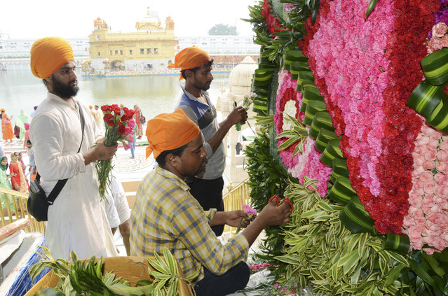 Indian devotees arrange flowers for decoration on the eve of the 415th anniversary of the installation of the Guru Granth Sahib (Sikh holy book) at the Golden Temple in Amritsar on August 30, 2019. (Photo by Narinder Nanu/AFP Photo)