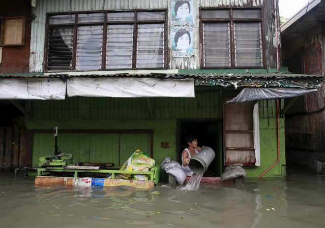 A woman clears flood water that entered her home, caused by typhoon Linfa, locally named Egay, at Longos town in Malabon city, north of Manila July 6, 2015. (Photo by Romeo Ranoco/Reuters)