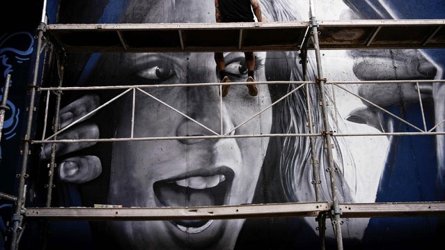 """A graffiti artist works on his piece during the International Graffiti Festival """"Meeting Of Styles"""", in Pristina on July 29, 2019. The International Meeting of Styles (MOS) is an international network of graffiti artists and aficionados that began in Wiesbaden, Germany, in 2002. (Photo by Armend Nimani/AFP Photo)"""