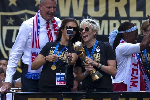 U.S. women's soccer players Megan Rapinoe (R) and Carli Lloyd (L) take a selfie with the Wold Cup trophy as they ride a float with New York City Mayor Bill de Blasio during the ticker tape parade up Broadway in lower Manhattan to celebrate their World Cup final win over Japan, in New York, July 10, 2015. (Photo by Mike Segar/Reuters)